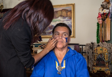 Diana Molina applies facepaint to Abe Sanchez