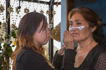 Gabriela Molina applies facepaint to Carmen Moreno, her mother